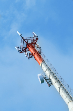 Cell  phone tower rises against a blue sky  photo