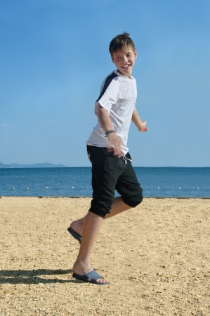 boy at the beach, running to swim in the ocean photo