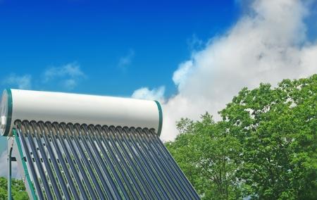 tuberias de agua: de agua solar sistema de calefacci�n en el techo de una casa sobre un fondo de cielo azul y verde bosque