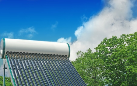 boiling water: solar water heating system on the roof of a house on a background of blue sky and green forest Stock Photo