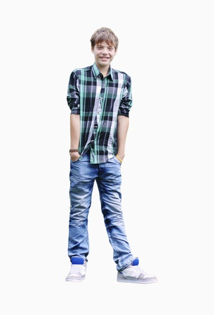 Young Boy in a Plaid Shirt stands hands in pockets on the white background photo