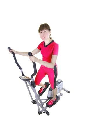 Fit woman on the xtrainer machine isolated on white Stock Photo - 16985031