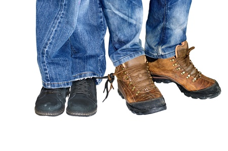 Two pairs of male and female legs in jeans with boots attached to each other laces - love forever photo