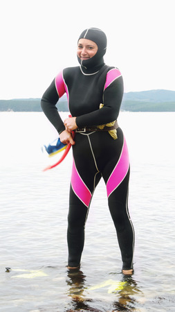 wetsuit: Woman Freediver in a diving suit ready to sail