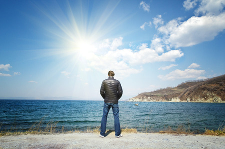 man in a black jacket standing on the sea