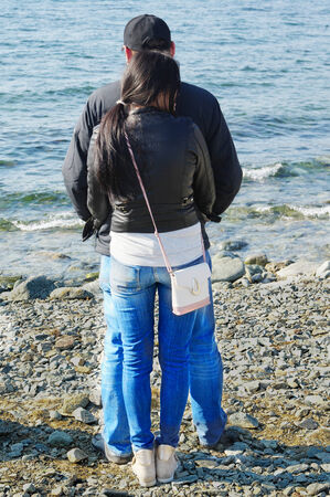 Back view of young couple standing on the beach. photo