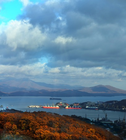 shipway: ships under loading in the port of Nakhodka on the background of clouds and yellow foliage