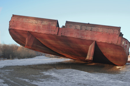 stranded: huge barge stranded at beach awaiting shipment of scrap metal