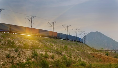 goods train: Freight train passing by on sunset beam