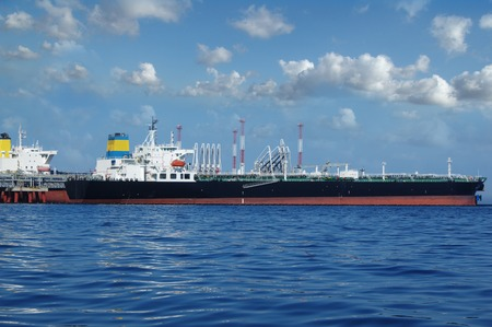 shipper: crude oil tanker is loading in the port on the background of clouds