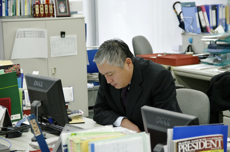 pay cuts: Depressed Asian businessman. Japanese office worker office Tokyo, Japan, 15.12.2009