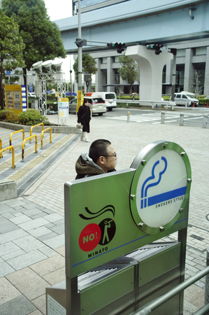 mid distance: Man smokers have a special machine that sucks the smoke in the streets of Tokyo, japan.15.12.2009