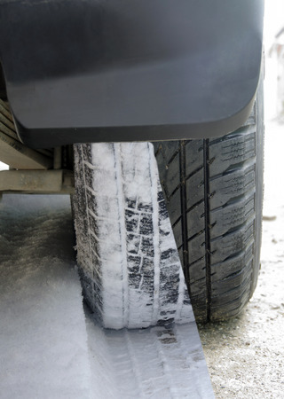 all weather: winter tires with snow and ice on blue background