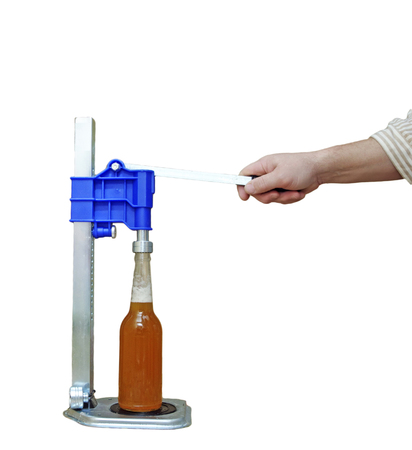 capping: Manual capping machine for bottles on a white background Stock Photo