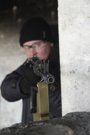 gunner: machine gunner in black uniforms and protective glasses aim of the shelter Stock Photo