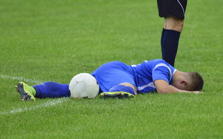 premiership: soccer player injured lying on the grass with a ball
