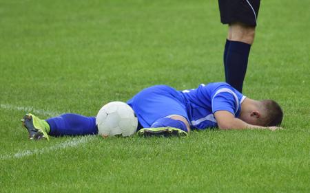 voetballer gewond liggend op het gras met een bal