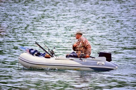 fisherman floats on an inflatable boat on a fishing trip Stock Photo