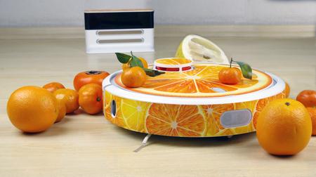 The automated robot vacuum cleaner stylized orange fruit on a white charging station background