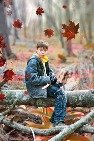 The boy sitting on a log in feral wood Banco de Imagens