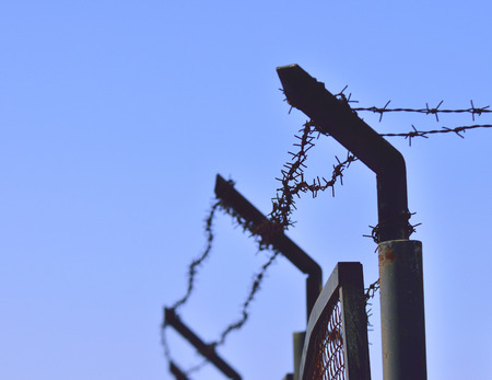 barbed wires On pillars against blue sky.