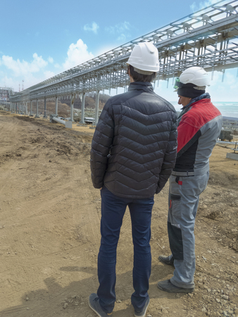 Two engineers discuss the construction of a trestle for pipes in an oil port
