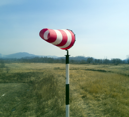 Red-white windsock indicating wind with blue sky Banco de Imagens