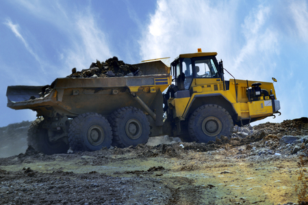 hauler: Big industrial tipper truck goes on mountain road, big roadworking tipper construction concept Stock Photo