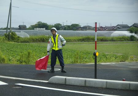 Japan road worker Stands on the side of the road with a flag