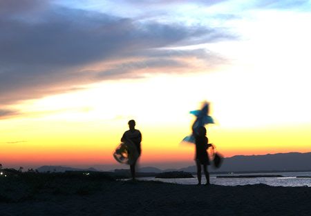 young guy and girl go on the beach at sunset and play swimming circles