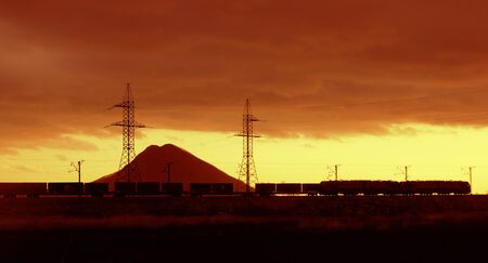 ontainer train is racing at sunset against the background of a mountain and towers with wires Banco de Imagens