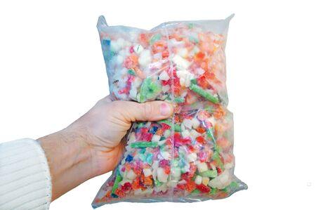 Mix of deep-frozen vegetables in cellophane package in hand. Banco de Imagens