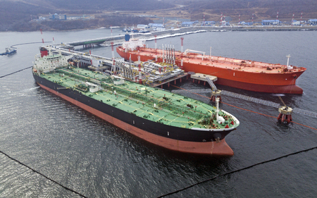 Aerial view of Oil tanker ship loading in port, Crude oil tanker ship under cargo operations on typical shore station with clearly visible mechanical loading arms and pipeline infrastructure.