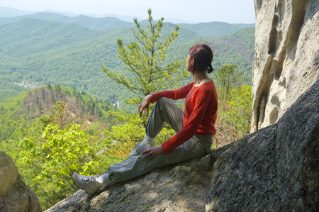 Woman traveler sits and looks at the edge of the cliff and looks at the valley