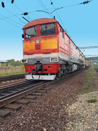 red diesel locomotive on the tracks in motion against a blue sky