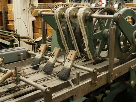Belts and brushes on ancient stitching machine in publishing house