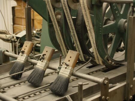 Brushes on ancient stitching machine in publishing house