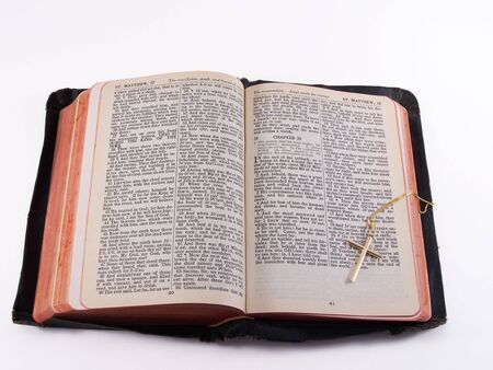 KJV Bible opened to Matthew 28, with gold cross on chain, isolated with