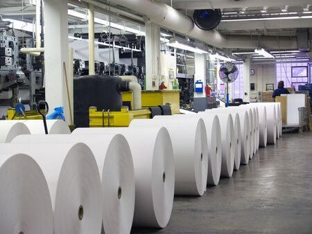 Rolls of paper waiting to be put on a printing press, visible in background 版權商用圖片