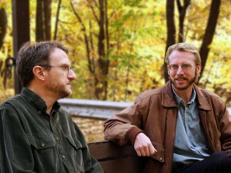 men, coworkers, colleagues, males, friends, pals, buddies, chums, bench park, seated lunch, discussion, serious, smile, trees, autumn, foliage, leaves, yellow, jacket, beard, mustache, glasses, talk, listen, chat, adults, two, nature Archivio Fotografico