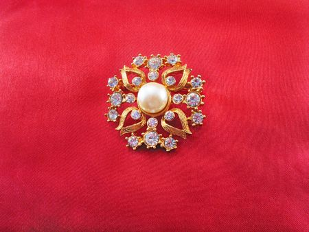 Gold brooch with pearl and blue stones on red fabric