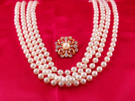 Strands of pearls on red fabric with pearl brooch
