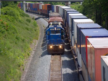 Locomotive pulling short train beside parked container cars