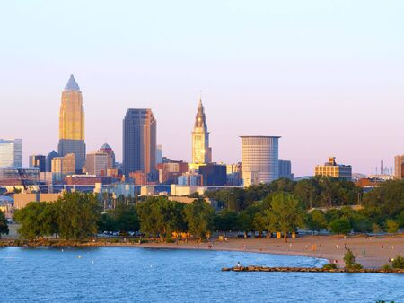 Downtown Cleveland, Ohio, lit by the setting sun, with beach in foreground