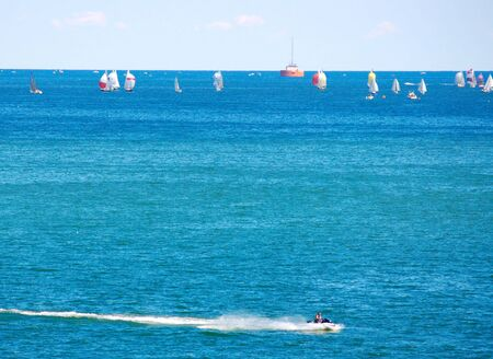 Sailboat race with speeding jetski in foreground