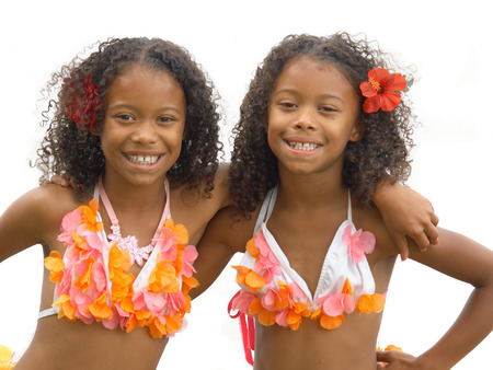 Identical twin sisters dressed up as hula girls Imagens