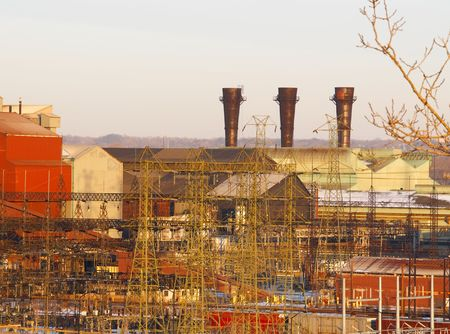 Old rust-belt steel mill with three chimneys in late afternoon light