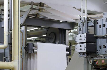 Paper threading its way through a printing press during a press run 写真素材