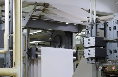 Paper threading its way through a printing press during a press run Imagens