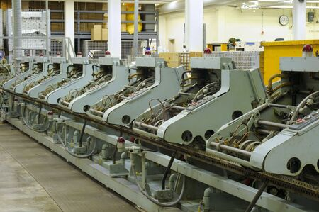 Row of stitching machines for binding booklets in a publishing house Foto de archivo